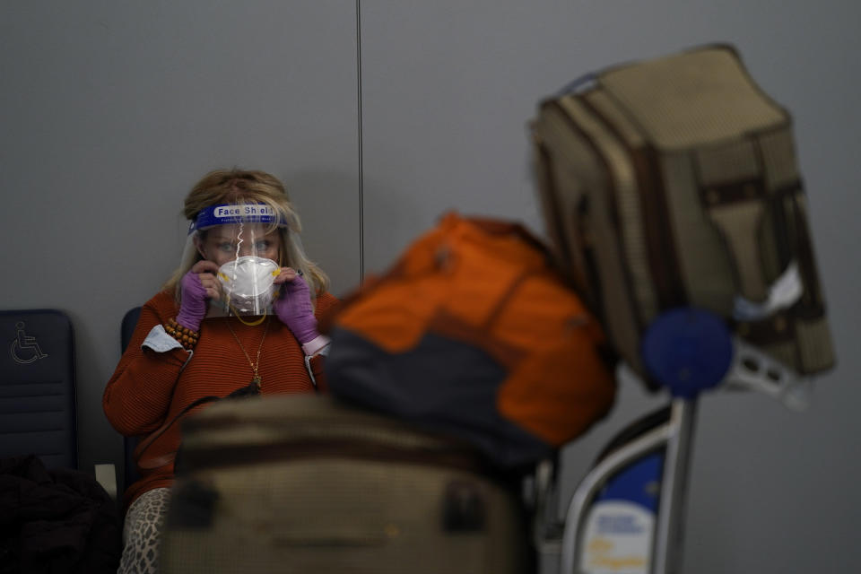 FILE - In this Nov. 23, 2020, file photo, a traveler adjusts her mask while waiting to check in for her flight at the Los Angeles International Airport in Los Angeles. Data from roadways and airports shows millions could not resist the urge to gather on Thanksgiving, even during a pandemic. (AP Photo/Jae C. Hong, File)