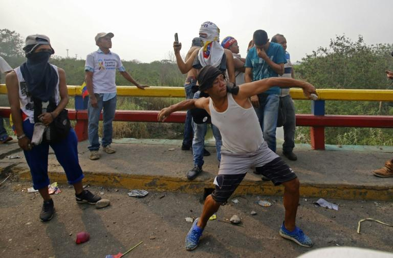 Demonstrators throw rocks at Venezuelan police after a truck with humanitarian aid was set on fire at the Francisco de Paula Santander international bridge linking Cucuta, Colombia, and Urena, Venezuela