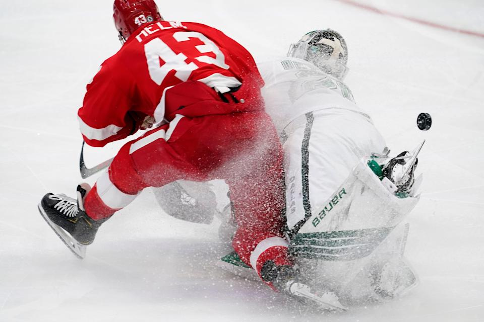 Detroit Red Wings left wing Darren Helm (43) and Dallas Stars goaltender Jake Oettinger collide on the ice as they two were trying to reach a loose puck in the third period in Dallas on Tuesday, April 20, 2021. Oettinger was charged with tripping on the play.