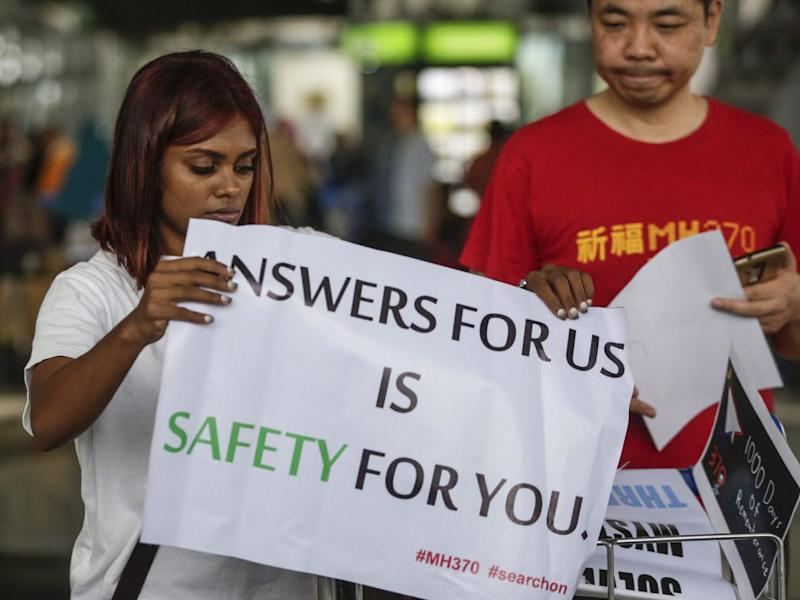 Malaysian Grace Subathirai Nathan (L), whose mother Anne Daisy was on board flight MH370, holds a banner with next-of-kin Jiang Hui of China: EPA