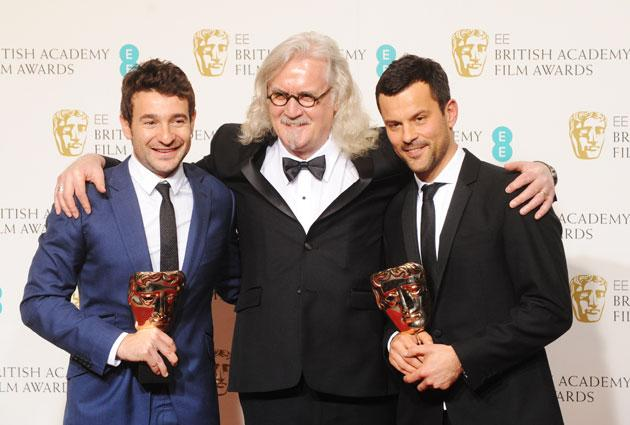 Bart Layton (L) and Dimitri Doganis, winners of the Outstanding Debut By A British Writer, Director or Producer award, pose with presenter Billy Connolly in the press room at the EE British Academy Film Awards at The Royal Opera House on February 10, 2013 in London, England. (Photo by Stuart Wilson/Getty Images)