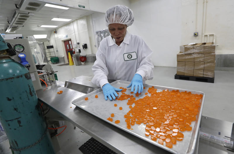 "Ioka Tasi works on packaging cannabis-infused mango hard candies at Evergreen Herbal, Wednesday, July 24, 2019, in Seattle. Washington state's marijuana regulators have eased some requirements regarding the ""seed to sale"" tracking of the drug, a week after a botched software update began preventing many business from being able to ship their products, cost hundreds of thousands of dollars in lost sales and prompted some to furlough workers. (AP Photo/Elaine Thompson)"
