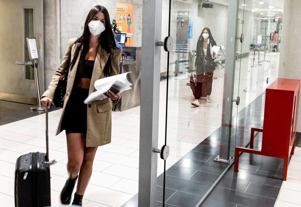 Mask-clad travellers walk with their luggage towards passport control upon arrival at Larnaca International Airport on June 9, 2020. - Cyprus opened back up for international tourism on June 9, with airports welcoming visitors after an almost three-month shutdown due to the COVID-19 coronavirus pandemic, with a bold plan to cover health care costs for visitors. (Photo by Iakovos HATZISTAVROU / AFP) (Photo by IAKOVOS HATZISTAVROU/AFP via Getty Images)