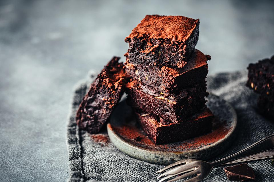 Pile of freshly made chocolate zucchini brownies garnished with cocoa powder on a round wooden plate. Delicious chocolate zucchini brownies served.