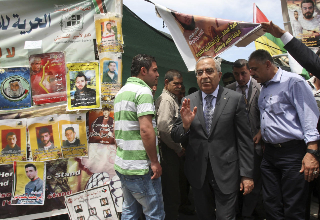 In this Sunday, May 6, 2012 photo, Palestinian Prime Minister Salam Fayyad leaves a tent set up in solidarity with Palestinian prisoners on hunger strike in Israeli jails, in the West Bank town of Nablus. According to Israel's Prison Service at least one-third of the 4,600 Palestinian prisoners in Israel began a collective hunger strike in mid-April 2012. (AP Photo/Nasser Ishtayeh)