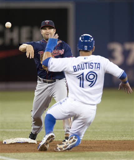 Minnesota Twins second baseman Brian Dozier forces out Toronto Blue Jays right fielder Jose Bautista as he turns a double play during the first inning of a baseball game in Toronto on Friday, July 5, 2013. (AP Photo/The Canadian Press, Frank Gunn)