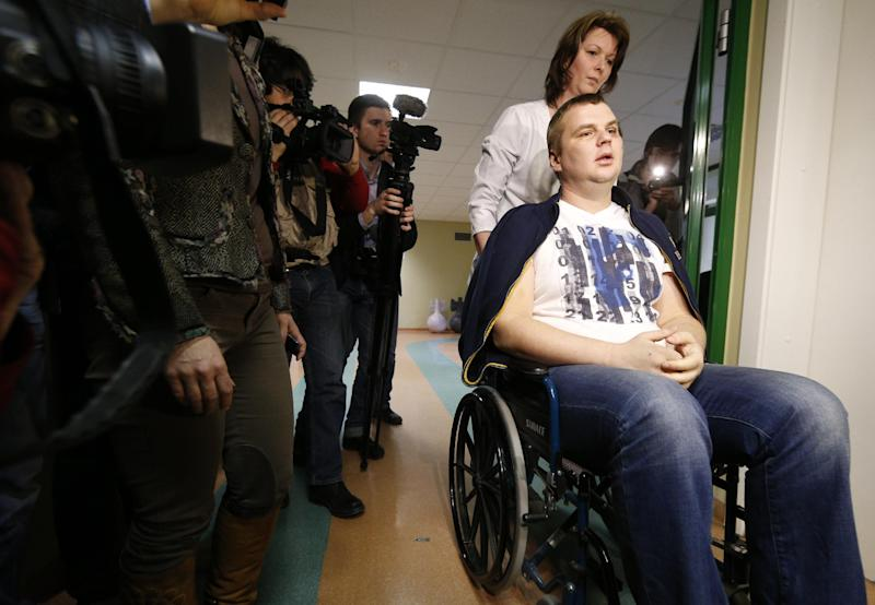 FILE - In this Thursday, Feb. 6, 2014 file photo, Ukrainian opposition activist Dmytro Bulatov is seen in a hospital after a press conference in Vilnius, Lithuania. Protest leader Dmytro Bulatov after being beaten and having a part of his ear cut off during the protests was appointed Youth and Sports Minister during a session in the Ukrainian parliament in Kiev, Ukraine, Thursday, Feb. 27, 2014. Top figures in Ukraine's three-month protest are taking up powerful posts in the new Cabinet, underscoring the powerful and unpredictable force of the revolt. But while few doubt the leaders' resolve, the nominations have raised questions about their skills and expertise — especially given the enormous challenges the new government faces. (AP Photo/Mindaugas Kulbis)