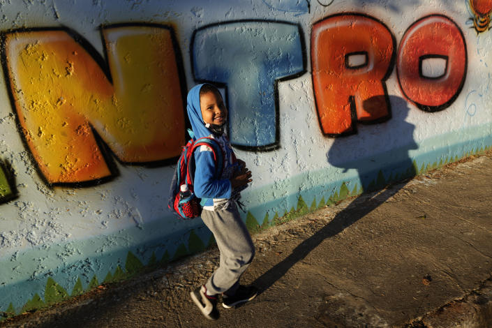 A student arrives for the first day back to in-person classes at a public school during the COVID-19 pandemic in Brasilia, Brazil, Thursday, Aug. 5, 2021, after a year and a half of remote learning. (AP Photo/Eraldo Peres)