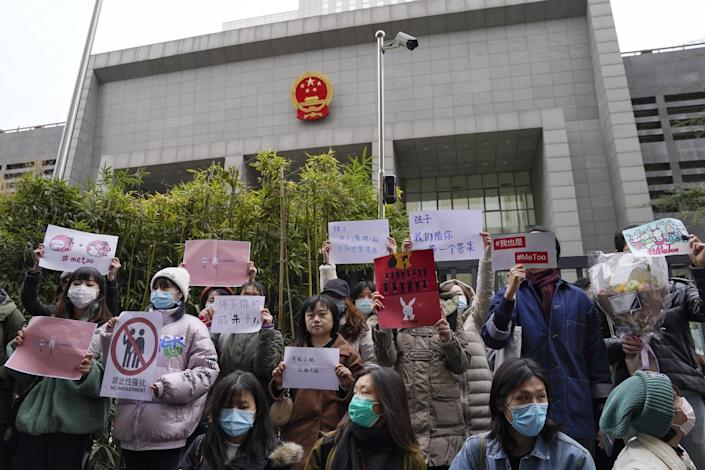 Supporters hold banners as they wait for #MeToo plaintiff Zhou Xiaoxuan outside at a courthouse in Beijing.