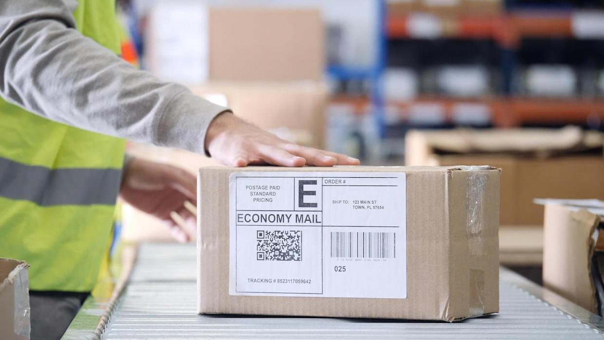 Unrecognizable distribution warehouse employee places a hand on a package ready for distribution.
