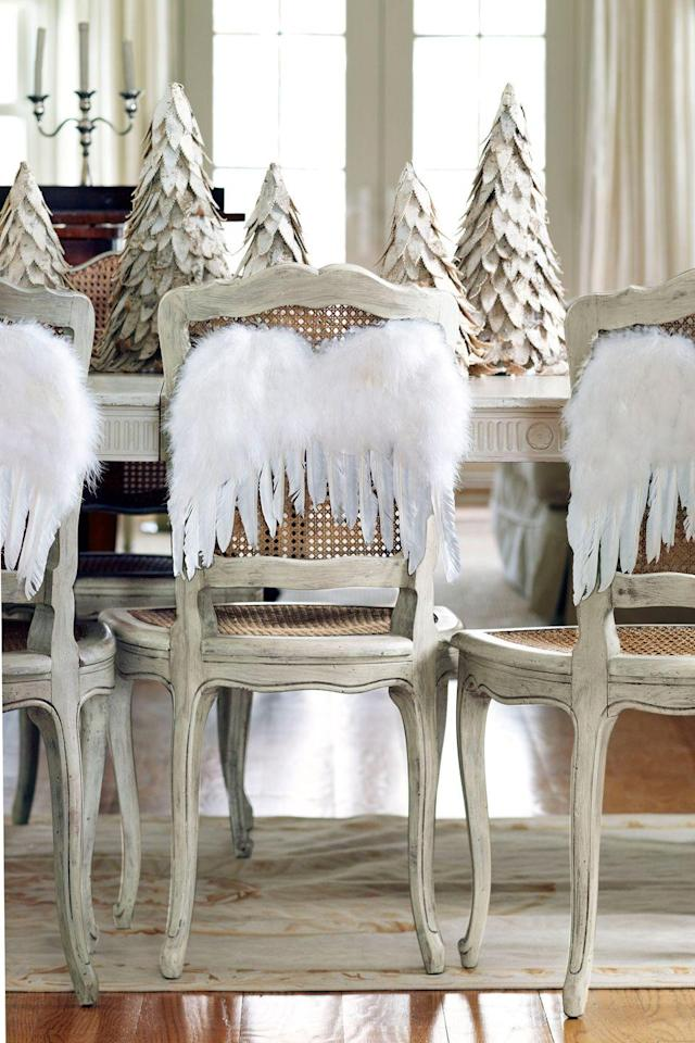 <p>A row of birch-bark trees makes for a simple yet stunning centerpiece. Dining chairs get into the holiday spirit with angel wings.</p>
