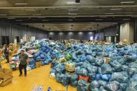 A person walks between donations in kind that are lying in a hall on the grounds of the Nuerburgring race track in Nuerburg, western Germany, Saturday, July 17, 2021. Heavy rains caused mudslides and flooding in the western part of Germany. Multiple have died and are missing as severe flooding in Germany and Belgium turned streams and streets into raging, debris-filled torrents that swept away cars and toppled houses. (Philipp von Ditfurth/dpa via AP)