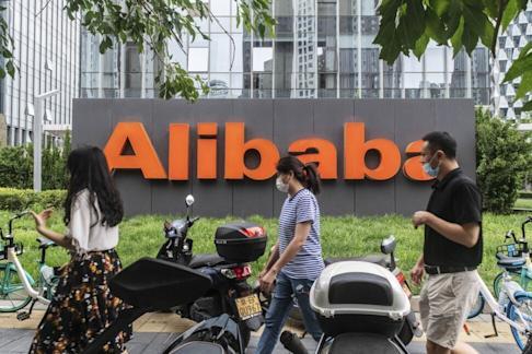 Pedestrians walk past Alibaba Group Holding's logo, displayed in front of the e-commerce giant's offices in Beijing, on August 19. Photo: Bloomberg