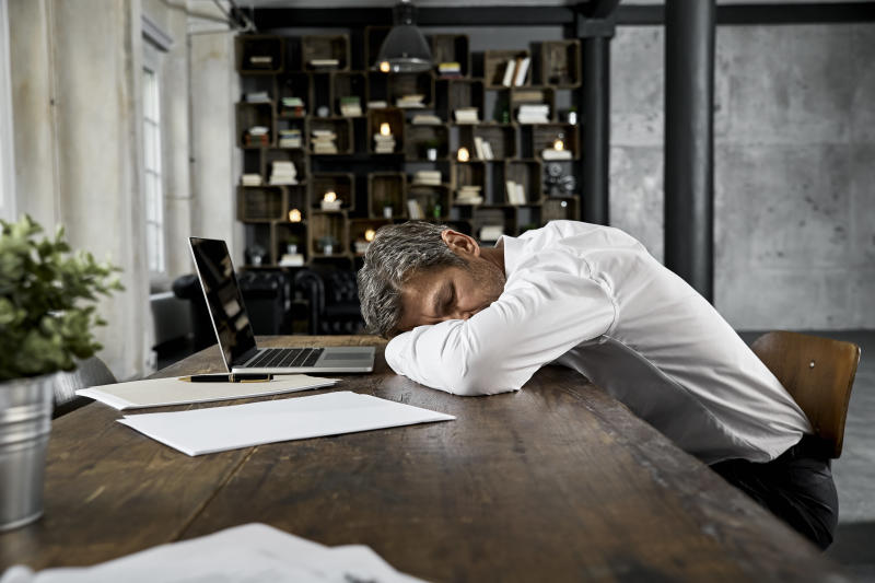 Mature businessman sleeping on desk in loft