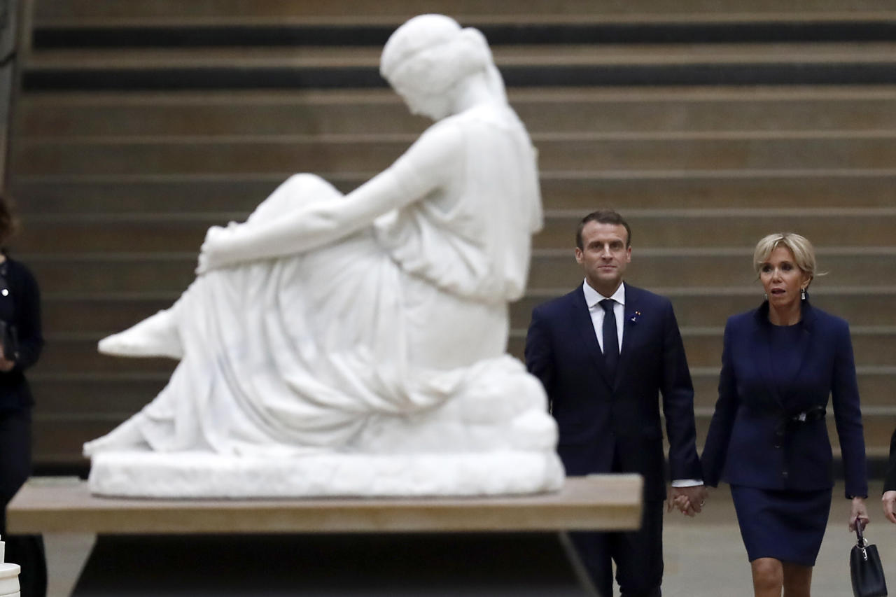 French president Emmanuel Macron and his wife Brigitte Macron arrive at the official dinner on the eve of the international ceremony for the Centenary of the WWI Armistice of 11 November 1918 at the Orsay Museum, in Paris, France, Saturday, Nov. 10, 2018. (Ian Langsdon/Pool Photo via AP)