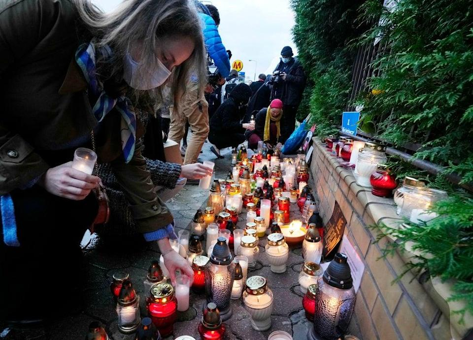 Warsaw residents place candles before the national Border Guards Headquarters in a sign of mourning for four migrants found dead over the weekend (AP)