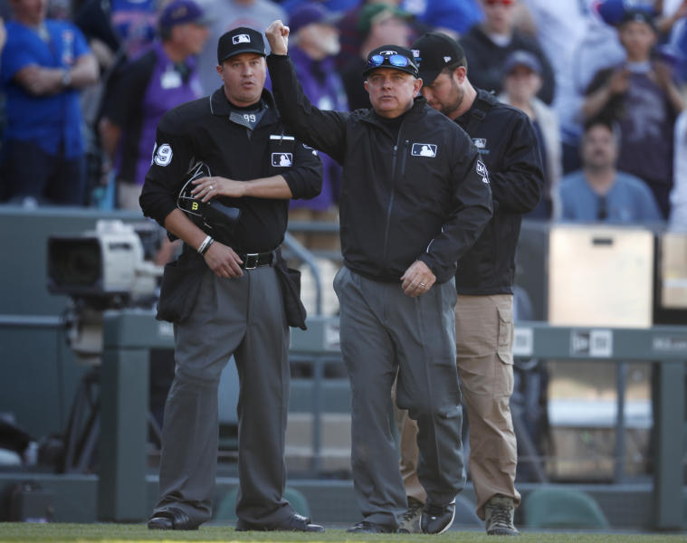 After reviewing the play, crew chief Greg Gibson, front signals that Nolan Arenado was out at home plate trying to advance on a pitch that bounded away from Chicago Cubs catcher Willson Contreras for the final out in the ninth inning of a baseball game Sunday, April 22, 2018, in Denver. Looking on at back left is home plate umpire Cory Blaser. The Cubs won 9-7. (AP Photo/David Zalubowski)