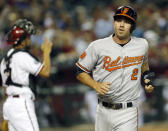 Baltimore Orioles' J.J. Hardy (2) scores on a base hit by teammate Brian Roberts as Arizona Diamondbacks catcher Wil Nieves looks away during the second inning, Monday, Aug. 12, 2013, in Phoenix. (AP Photo/Matt York)