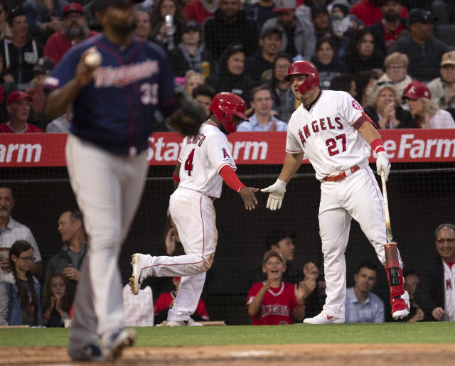 Los Angeles Angels' Luis Rengifo, center, is being greeted by Mike Trout after scoring on a wild pitch during the second inning of a baseball game against the Minnesota Twins in Anaheim, Calif., Tuesday, May 21, 2019. (AP Photo/Kyusung Gong)