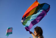 A person waves a rainbow flag during the Bucharest Pride 2021 in Bucharest, Romania, Saturday, Aug. 14, 2021. The 20th anniversary of the abolishment of Article 200, which authorized prison sentences of up to five years for same-sex relations, was one cause for celebration during the gay pride parade and festival held in Romania's capital this month. People danced, waved rainbow flags and watched performances at Bucharest Pride 2021, an event that would have been unimaginable a generation earlier. (AP Photo/Vadim Ghirda)