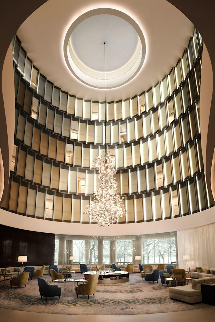 """A homage to the Hanseatic city of Hamburg, The Fontenay opened its doors in March and is poised to greet visitors this summer with its take on modern classicism. The 130-room """"hotel in the park"""" is the vision of architect Jan Störmer, who envisioned its amorphous, fluid-like shape with porcelain façade panels. All rooms have rounded corridors, in keeping with the principles of Feng Shui. The interiors, done by Christian Meinert, are clad in tones of light beige, green onyx, white, and royal blue. <a href=""""https://www.thefontenay.de/"""" rel=""""nofollow noopener"""" target=""""_blank"""" data-ylk=""""slk:thefontenay.de"""" class=""""link rapid-noclick-resp"""">thefontenay.de</a>"""