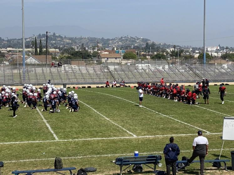Players for Garfield, left, and Banning gather before a scrimmage April 3, 2021.