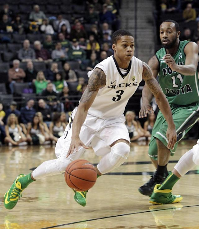 Oregon guard Joseph Young, left, drives past North Dakota guard Jamal Webb during the first half of an NCAA college basketball game in Eugene, Ore., Saturday, Nov. 30, 2013. (AP Photo/Don Ryan)