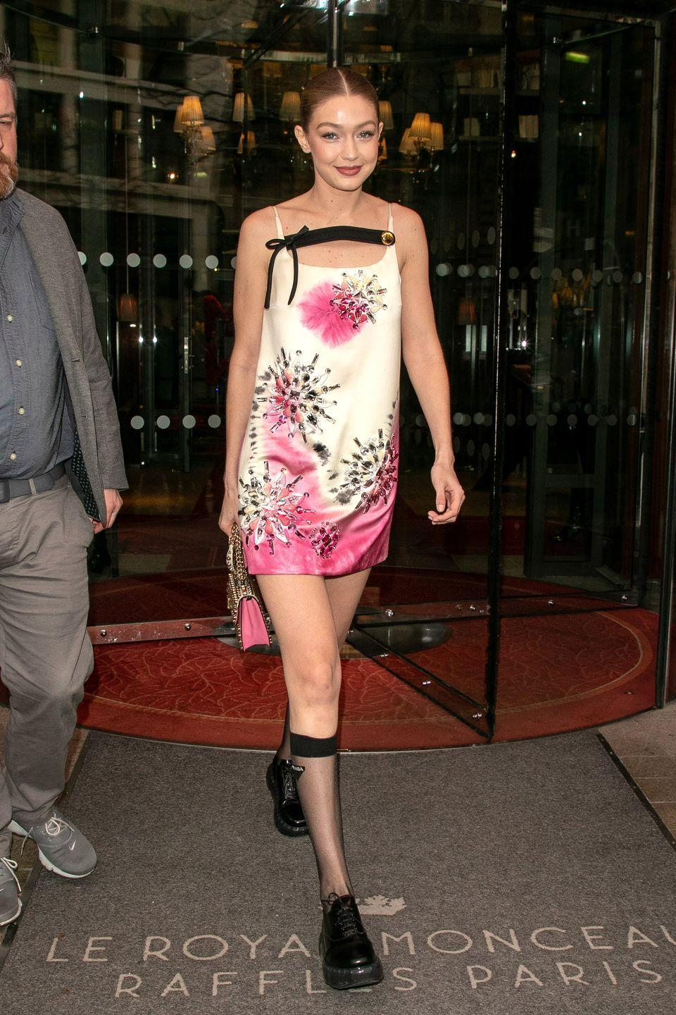 <p>In a creme and pink embellished mini dress, complementary handbag, and black shoes with sheer socks. </p>