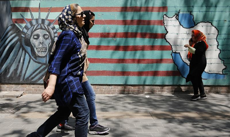 People walk by murals on the wall of the former US embassy in the Iranian capital Tehran on August 7, 2018 after US President Donald Trump warned countries against doing business with Iran (AFP Photo/Atta KENARE)