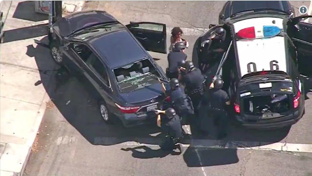 <p>Los Angeles Police officers remove a woman passenger from a car that crashed after a pursuit, and the driver ran into a nearby Trader Joe's supermarket, starting a hostage situation in the Silverlake district of Los Angeles on Saturday. (Photo: KNBC-TV via AP) </p>