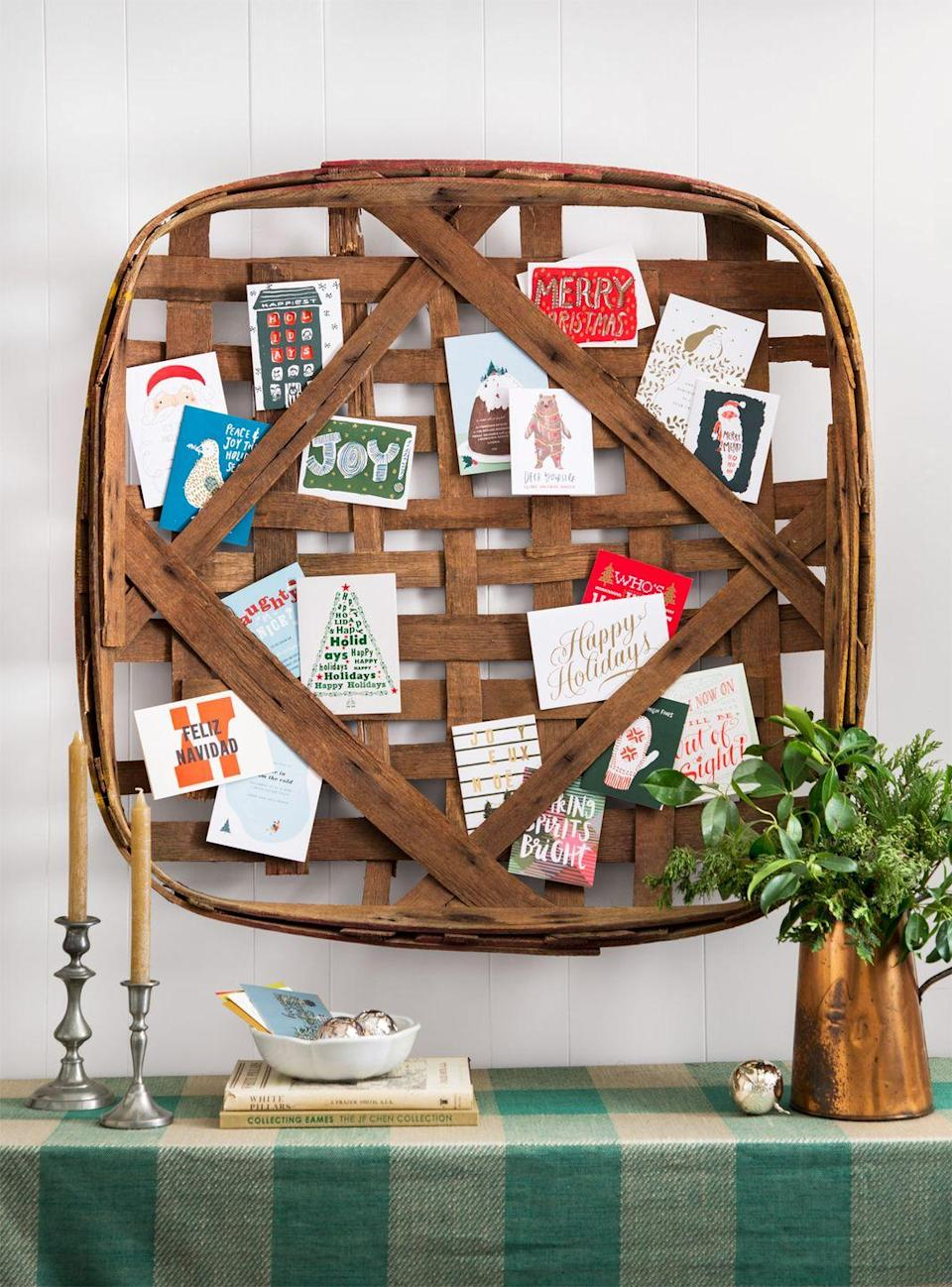 """<p>Show off the influx of season's greetings on a vintage tobacco basket by tucking well wishes into the overlapping strips of reed. (For old baskets, try <a href=""""https://www.ebay.com/"""" rel=""""nofollow noopener"""" target=""""_blank"""" data-ylk=""""slk:eBay"""" class=""""link rapid-noclick-resp"""">eBay</a>, <a href=""""https://www.etsy.com/"""" rel=""""nofollow noopener"""" target=""""_blank"""" data-ylk=""""slk:Etsy"""" class=""""link rapid-noclick-resp"""">Etsy</a>, or <em>CL</em> Fair vendor <a href=""""http://www.greatstuffbypaul.com/"""" rel=""""nofollow noopener"""" target=""""_blank"""" data-ylk=""""slk:Great Stuff By Paul"""" class=""""link rapid-noclick-resp"""">Great Stuff By Paul</a>). </p>"""