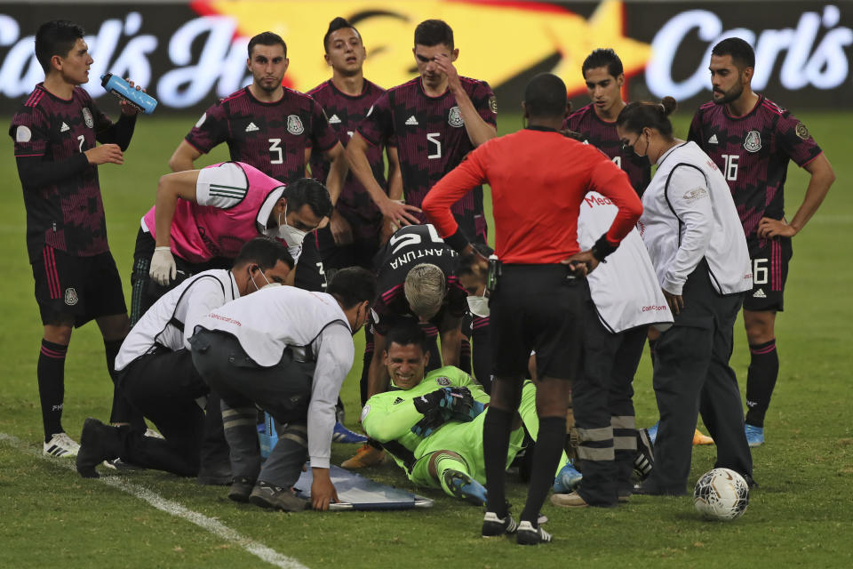 Mexico's goalkeeper Luis Malagon lies on the pitch in pain surrounded by teammates during a Concacaf Men's Olympic Qualifying championship soccer match against United States in Guadalajara, Mexico, Wednesday, March 24, 2021. (AP Photo/Fernando Llano)