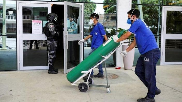 A worker arrives with an oxygen cylinder at Getulio Vargas hospital, amid the coronavirus disease