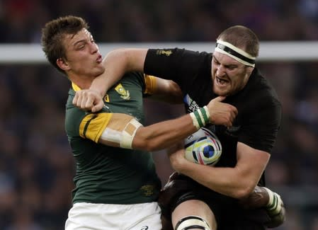 Retallick of New Zealand protects the ball from Pollard of South Africa during their Rugby World Cup semi-final at Twickenham in London