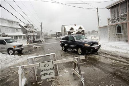 A jeep drives through the water on Lighthouse Road during a winter nor'easter snow storm in Scituate, Massachusetts January 3, 2014. REUTERS/Dominick Reuter