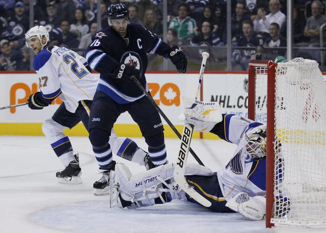 St. Louis Blues goaltender Brian Elliot gets tangled in Winnipeg Jets' Andrew Ladd (16) stick during the second period of an NHL hockey game, Friday, Oct. 18, 2013 in Winnipeg, Manitoba. (AP Photo/The Canadian Press, John Woods)