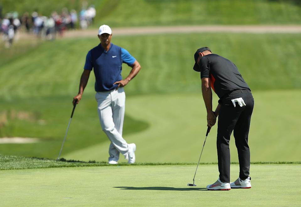 Brooks Koepka of the United States putts as Tiger Woods of the United States looks on during the first round of the 2019 PGA Championship at the Bethpage Black course. (Getty Images)