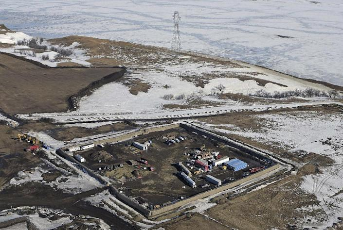 """FILE - In this Feb. 13, 2017, aerial file photo shows the site where the final phase of the Dakota Access pipeline will take place with boring equipment routing the pipeline underground and across Lake Oahe to connect with the existing pipeline in Emmons County near Cannon Ball, N.D. Environmental activists who tried to disrupt some oil pipeline operations in four states to protest the pipeline say they aren't responsible for any recent attacks on that pipeline. Dakota Access developer Energy Transfer Partners said in court documents Monday, March 20, 2017, that there have been """"coordinated physical attacks"""" along the $3.8 billion pipeline that will carry oil from North Dakota to Illinois. (Tom Stromme/The Bismarck Tribune via AP, File)"""