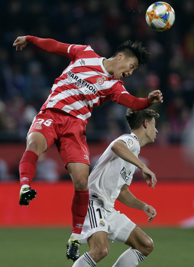 Real Madrid's Marcos Llorente, right, duels for the ball with Girona's Paik Seung-ho during a Spanish Copa del Rey soccer match between Girona and Real Madrid at the Montilivi stadium in Girona, Spain, Thursday, Jan. 31, 2019. (AP Photo/Manu Fernandez)