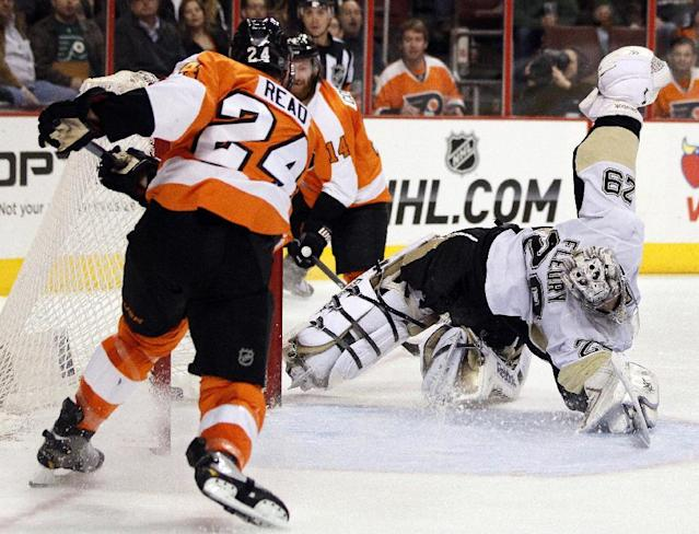 Philadelphia Flyers' Mattt Read, left, scores against a diving Pittsburgh Penguins goalie Marc-Andre Fleury during the second period of an NHL hockey game, Saturday, March 15, 2014, in Philadelphia. (AP Photo/Tom Mihalek)