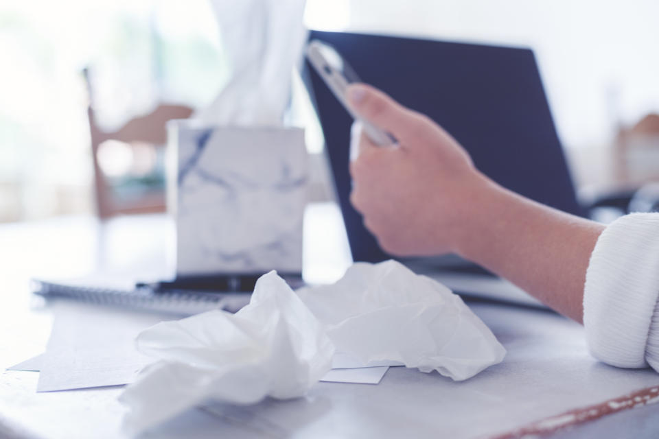 Woman with a cold or flu or allergy working at home. She is holding a mobile phone and is also using a laptop computer. She is sitting at the dining table which has paperwork on it.