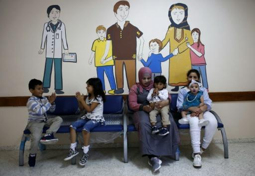 Palestinians wait at an UNRWA clinic in the southern West Bank city of Hebron on August 9, 2018