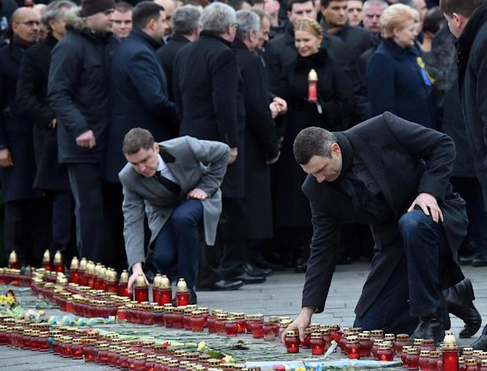 Mayor of Kiev Vitali Klitschko (R) sets a candle on the ground during the ceremony in Kiev on February 22, 2015 to mark the first anniversary of the killing of dozens of protesters in the Maidan (AFP Photo/Sergei Supinsky)