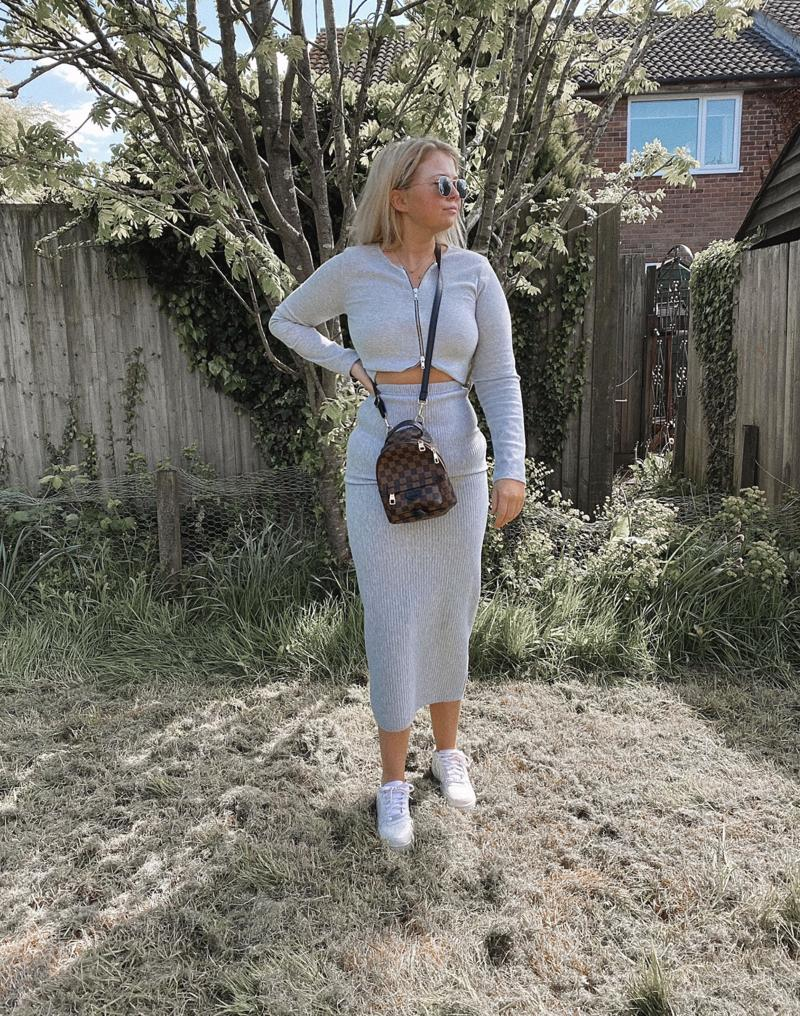 Woman in a grey skirt and top