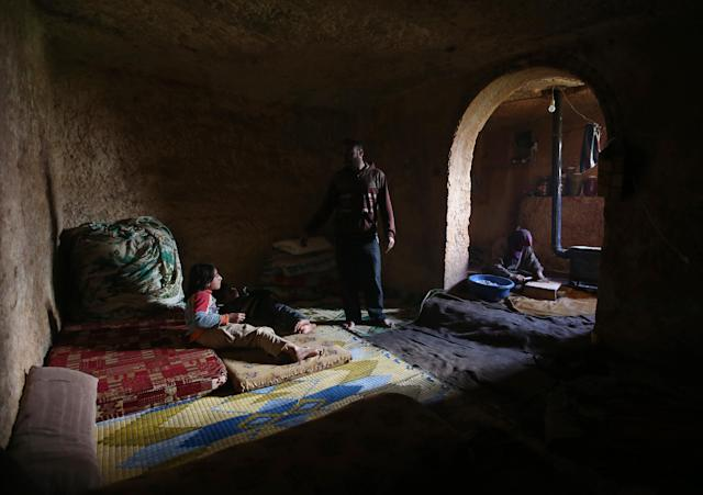 Sami, 32, center, speaks with his children at an underground Roman tomb which he uses with his family as shelter from Syrian government forces shelling and airstrikes, at Jabal al-Zaweya, in Idlib province, Syria, Thursday Feb. 28, 2013. Across northern Syria, rebels, soldiers, and civilians are making use of the country's wealth of ancient and medieval antiquities to protect themselves from Syria's two-year-old war. They are built of thick stone that has already withstood centuries, and are often located in strategic locations overlooking towns and roads. (AP Photo/Hussein Malla)