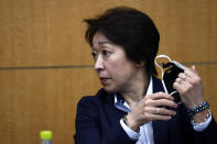 President of the Tokyo 2020 Olympics Organizing Committee Seiko Hashimoto removes her face mask as she attends the opening remark session of a press briefing on the operation and media coverage of Tokyo 2020 Olympic Torch Relay in Tokyo Thursday, Feb. 25, 2021. (Behrouz Mehri/Pool Photo via AP)