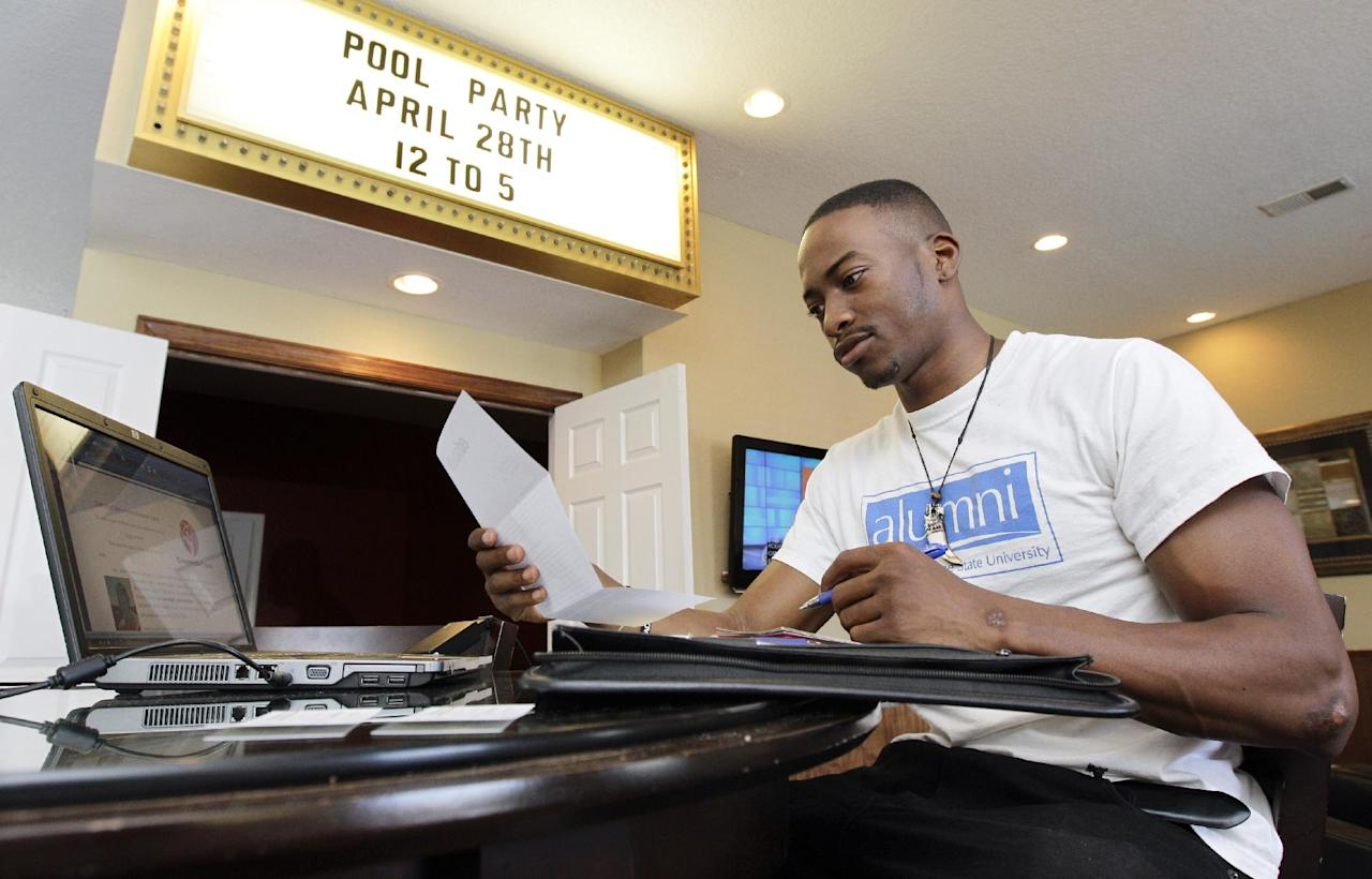 In this photo taken Thursday, April 19, 2012, Kelman Edwards Jr. works on his laptop in an apartment complex clubhouse near the campus of Middle Tennessee State University in Murfreesboro,Tenn., as he searches for a job. The college class of 2012 is in for a rude welcome to the world of work. A weak labor market already has left half of young college grads either jobless or underemployed in positions that don't fully use their skills and knowledge. (AP Photo/Mark Humphrey)