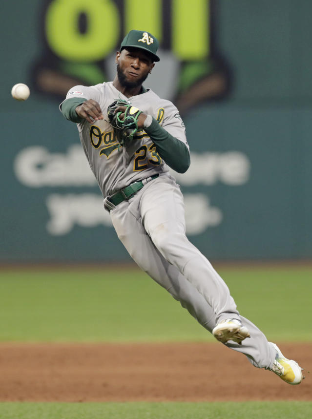 Oakland Athletics' Jurickson Profar throws out Cleveland Indians' Francisco Lindor at first base in the sixth inning of a baseball game, Tuesday, May 21, 2019, in Cleveland. (AP Photo/Tony Dejak)