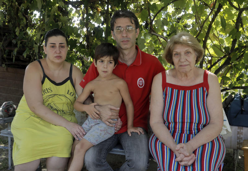 In this photo taken on Tuesday, Aug. 6, 2013, former Azerbaijani police officer Emin Akhmedbekov, 46, second right, poses for a photo with his family in a small village outside Kiev, Ukraine. Left to right are his wife Nigyar, 38, son Rauf, 5, and mother Maisa Guseinova, 75. Akhmedbekov fled to Ukraine, fearing persecution for his numerous lawsuits against Azerbaijani authorities, and hoping to find refuge in one of the freer ex-Soviet republics. Instead, the family found itself holed up in the small village with little hope of getting asylum and terrified of being sent back. (AP Photo/Efrem Lukatsky)
