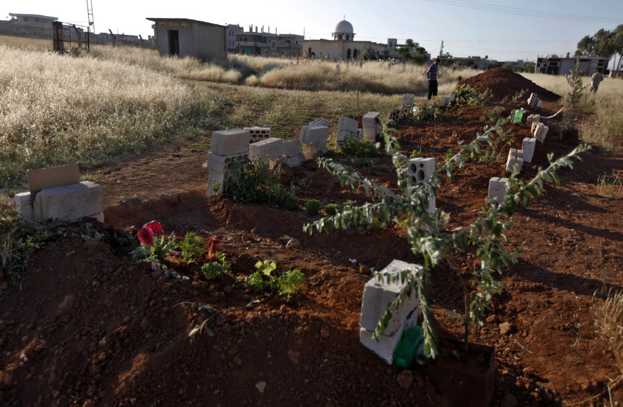 In a Tuesday, June 5, 2012 photo, a Syrian man stands next to a grave of 40 Syrians were killed in a military raid by the Syrian army in April 2012, in the town of Taftanaz,15 kilometers east of Idlib, Syria. At dawn on April 3, Syrian forces shelled the town in the first volley of what residents say was a massive assault after a string of large protests calling for the end of the autocratic rule of President Bashar Assad. (AP Photo/Khalil Hamra)